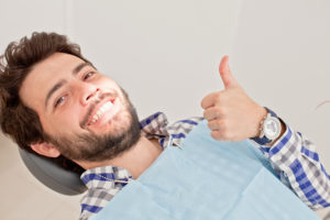 man smiling sitting in dentist chair
