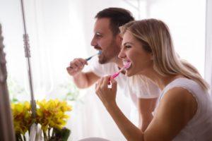 Couple brushing teeth together.